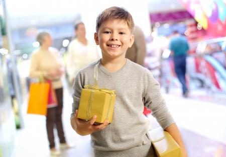ni�os de compras: Retrato de ni�o feliz con caja de regalo con su familia en el fondo