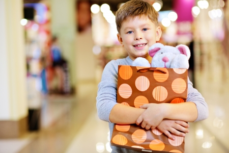 paperbag: Portrait of happy child holding paperbag with teddy bear and looking at camera Stock Photo