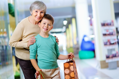 Portrait of happy child holding paperbag with his grandmother near by photo