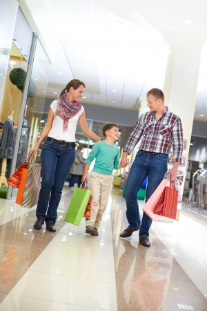 ni�os de compras: Retrato de familia caminando con bolsas de papel en el centro comercial Foto de archivo