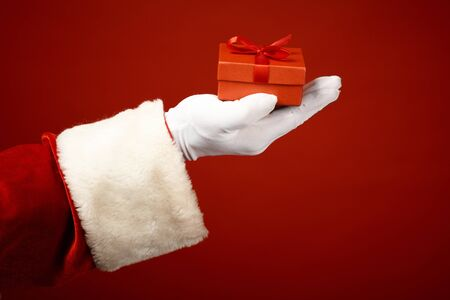 gloved: Photo of Santa Claus gloved hand with small red giftbox Stock Photo