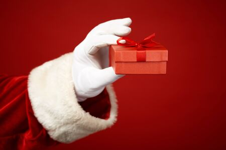 giftbox: Photo of Santa Claus gloved hand holding small red giftbox
