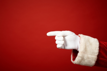 gloved: Photo of Santa Claus gloved hand in pointing gesture Stock Photo