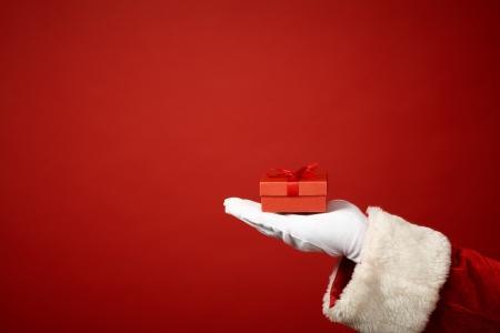 Foto van Santa Claus gehandschoende hand met kleine rode giftbox Stockfoto