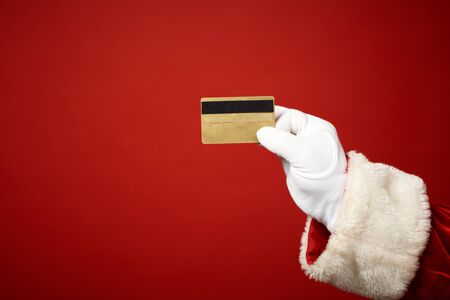 card payment: Photo of Santa Claus gloved hand holding credit card Stock Photo