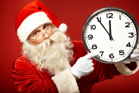 haste: Photo of Santa holding clock showing five minutes to midnight Stock Photo