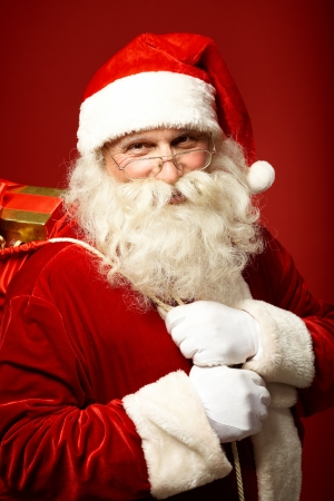 santa  claus: Portrait of happy Santa Claus holding sack with gifts and looking at camera