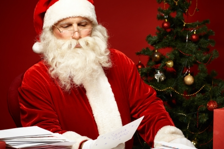 Portrait of Santa Claus looking at envelope in his hands photo