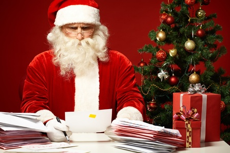 Portrait of confused Santa Claus looking at envelope in his hands photo