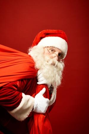 santa cap: Portrait of Santa Claus carrying huge red sack and looking at camera Stock Photo