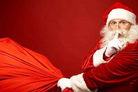 집게 손가락: 자신의 입으로 큰 빨간 자루 유지 집게 손가락으로 산타 클로스의 초상화 카메라를 찾고