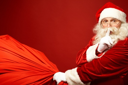 traditional events: Portrait of Santa Claus with huge red sack keeping forefinger by his mouth and looking at camera Stock Photo