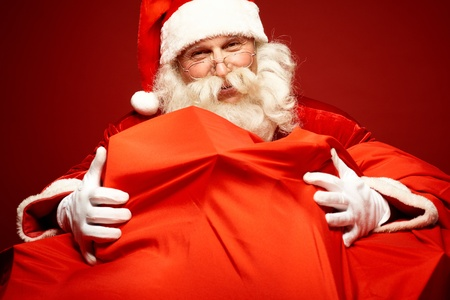 huge: Portrait of Santa Claus embracing huge red sack with gifts Stock Photo