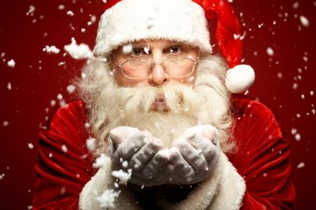 Photo of Santa Claus in eyeglasses blowing snow and looking at camera