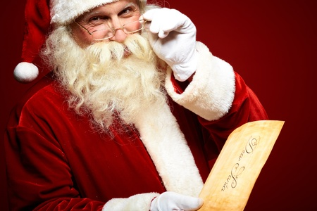 Portrait of happy Santa Claus holding Christmas letter in his hands and looking at camera photo