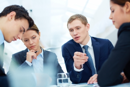 Attentive business partners listening to new ideas and thinking them over at meeting Stock Photo