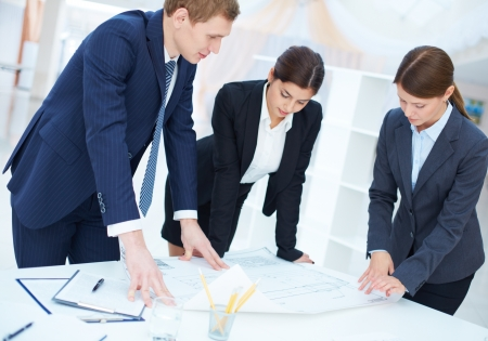 BUSY OFFICE: Team of three engineers discussing blueprint at meeting Stock Photo