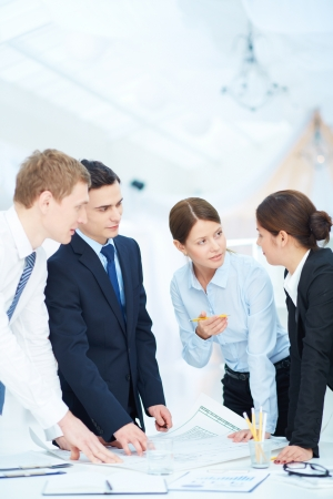 serious meeting: Team of engineers discussing blueprint at meeting Stock Photo