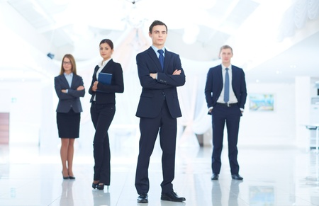 young executives: Portrait of young businessman looking at camera with elegant partners on background Stock Photo