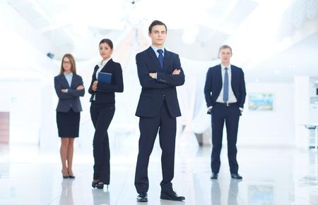 empresario: Retrato de hombre de negocios joven mirando a la c�mara con los socios elegantes en el fondo Foto de archivo