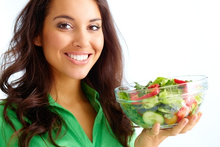 lifestyle looking lovely: Close-up of pretty girl holding fresh vegetable salad in glass bowl