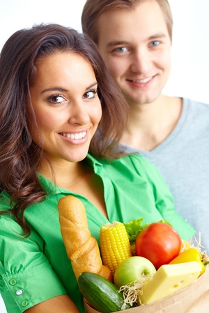 vital: Happy female with healthy food looking at camera with young man on background
