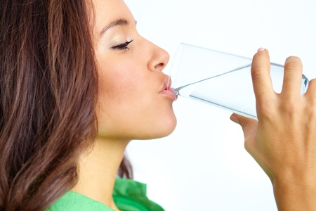 Close-up of pretty girl drinking water from glass photo