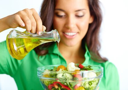 beautiful salad: Close-up of pretty girl pouring oil into vegetable salad in glass bowl