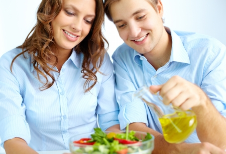 Happy man pouring oil into vegetable salad with his wife near by photo