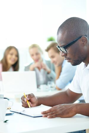 study group: Portrait of cute African guy planning work with group of partners on background