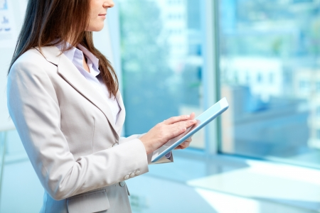 competitive business: Close-up of businesswoman working with touchpad in office