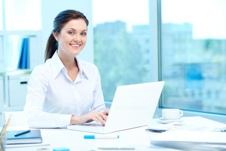 secretaria: Retrato de joven empresaria escribiendo en la computadora portátil