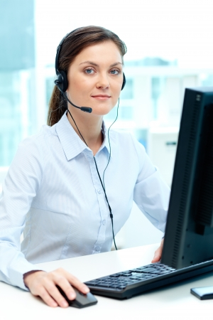 telephony: Portrait of young businesswoman with headset typing on computer keyboard