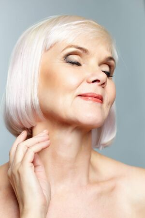 congenial: Portrait of aged female in delight over grey background