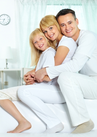 siting: Portrait of happy parents and their daughter siting on sofa and looking at camera Stock Photo