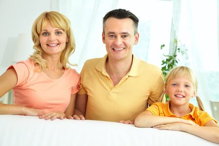 Portrait of happy parents and their daughter looking at camera with smiles  Stock Photo - 16085630