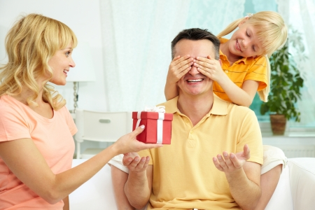 guess: Portrait of cute girl closing male eyes by hands and happy woman holding gift for him Stock Photo