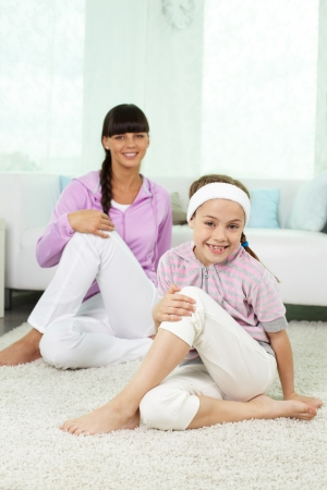 Portrait of little girl and her mother doing physical exercise for stretching photo