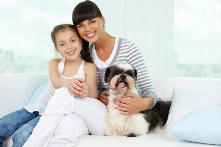 Portrait of happy girl and her mother with shih-tzu dog looking at camera photo