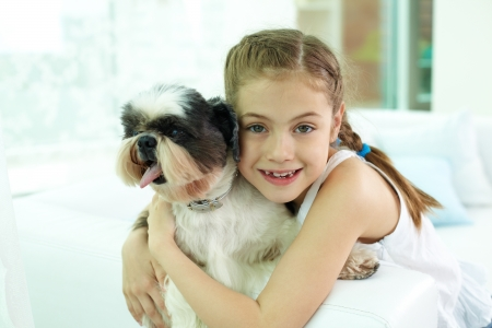 shihtzu: Portrait of happy girl embracing shih-tzu dog and looking at camera