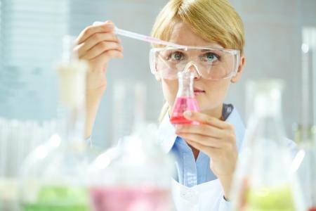 investigador cientifico: Un qu�mico joven con tubo con l�quido durante el experimento qu�mico Foto de archivo