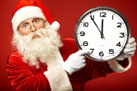 Photo of stunned Santa holding clock showing five minutes to midnight photo