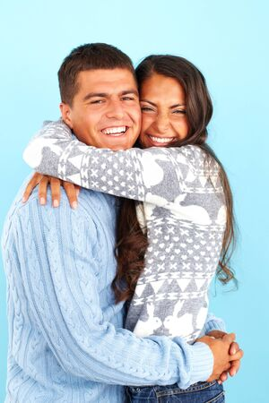 pullovers: Portrait of happy couple in fashionable pullovers embracing and looking at camera  Stock Photo