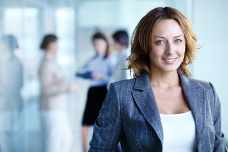 foreground: Image of pretty businesswoman looking at camera
