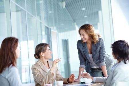 Image of four businesswomen interacting at meeting Stock Photo