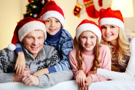 Portrait of four happy family members in Santa caps looking at camera with smiles Stock Photo - 16304951