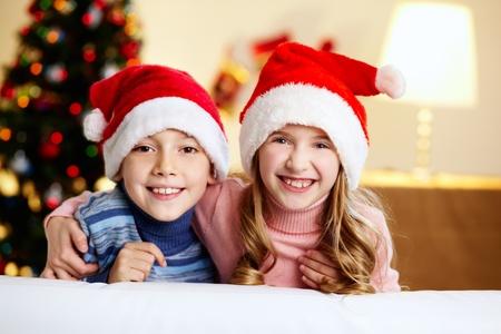 Adorable siblings in Santa hats smiling and looking at camera photo