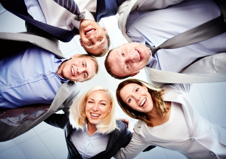 Below view of several happy business partners looking at camera while embracing each other Stock Photo - 16304957