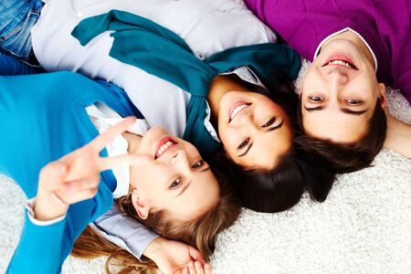 Above angle of attractive friends looking at camera and smiling Stock Photo - 16221840