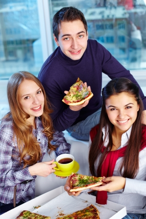 Image of teenage friends eating pizza together photo